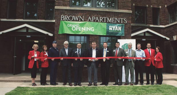 Team gathers for a ribbon cutting ceremony in front of Brown Apartments